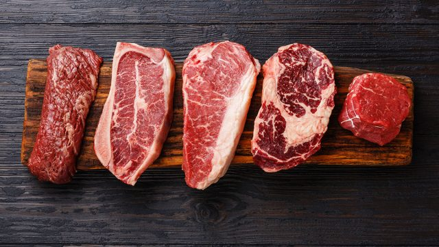 slabs of different cuts of red meat on wooden cutting board