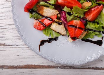 plated salad of lettuce strawberries chicken with balsamic vinaigrette