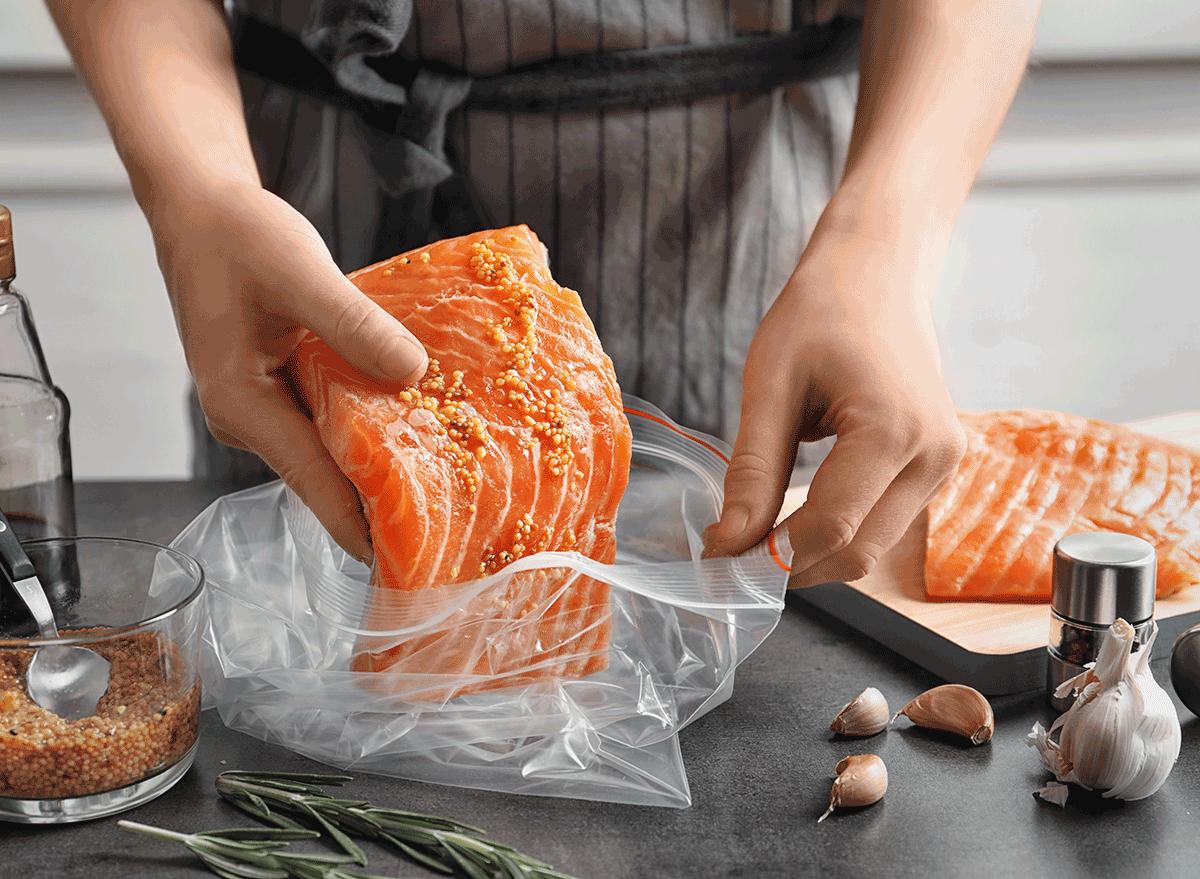 woman preparing salmon before cooking