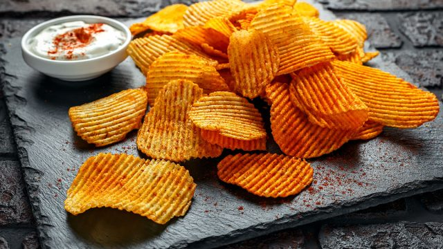 smoked paprika potato chips on black plate with dipping sauce