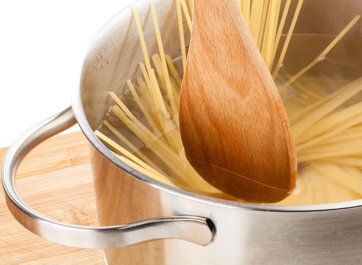 wooden spoon stirring pasta
