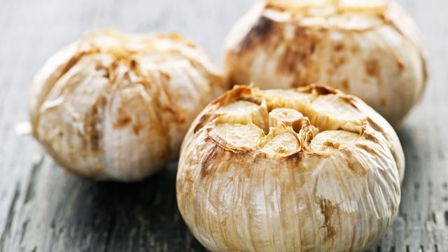 three cloves of roasted garlic on table