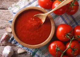 tomato sauce in wooden bowl with wooden spoon