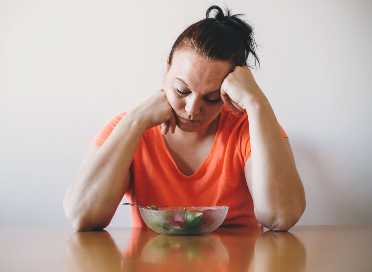 Unhappy woman doesnt want to eat salad or a healthy diet - always hungry reasons