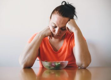 Unhappy woman doesnt want to eat salad or a healthy diet