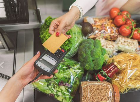 Woman paying for her vegetable vegan groceries at a checkout