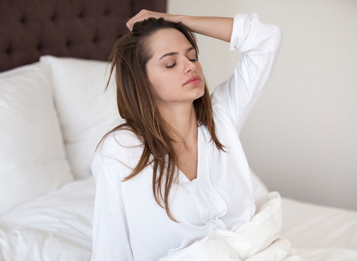woman in bed holding head - how does alcohol affect the brain