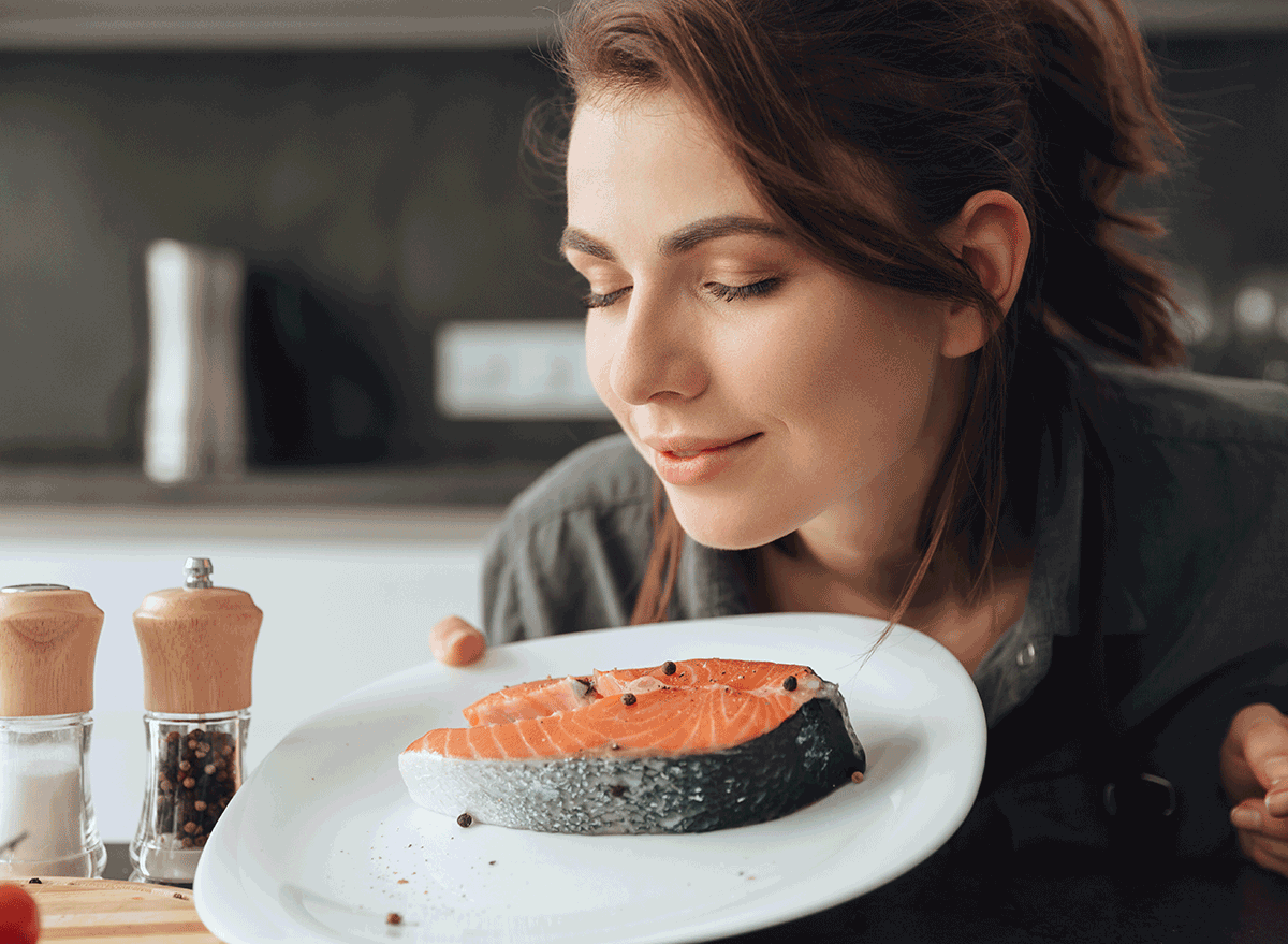 woman smelling piece of salmon