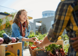 woman smiling buying sustainable food from stand