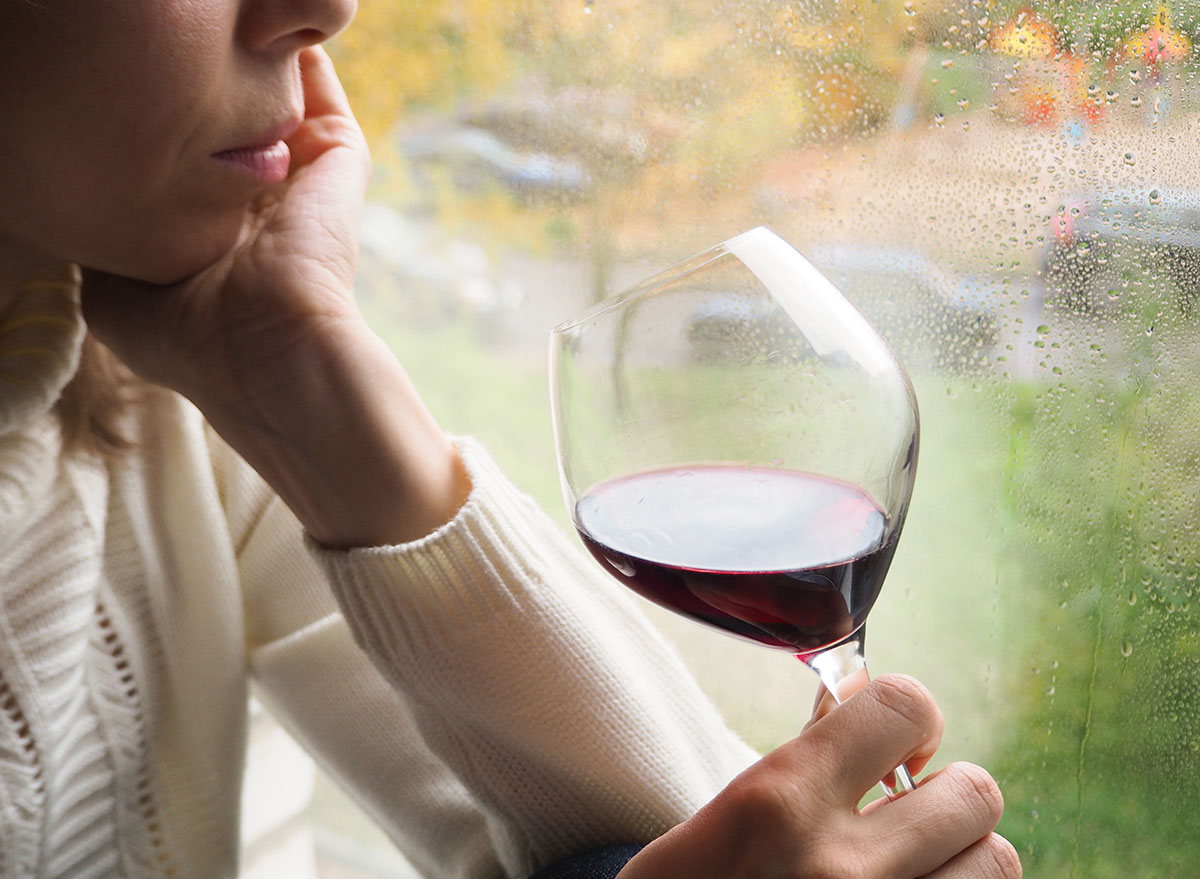 woman drinking wine by window - how does alcohol affect the brain