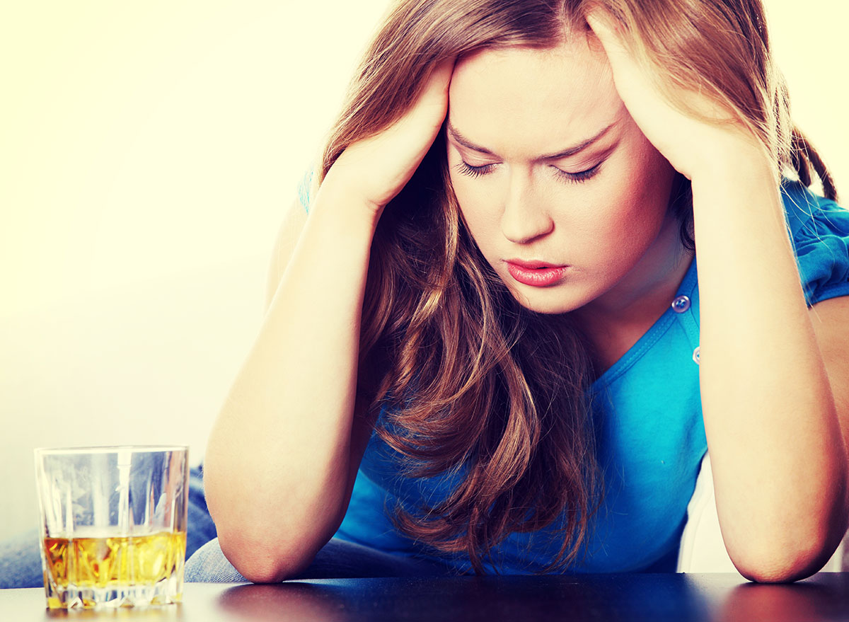 woman holding head from alcohol - how does alcohol affect the brain