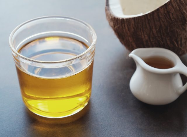 MCT oil in glass cup with half of coconut