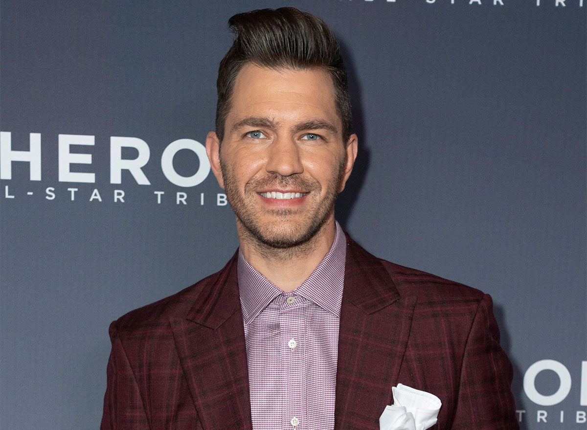 andy grammer on step and repeat wearing purple shirt and white pocket square