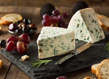 blue cheese on cheese board with crostinis and purple grapes