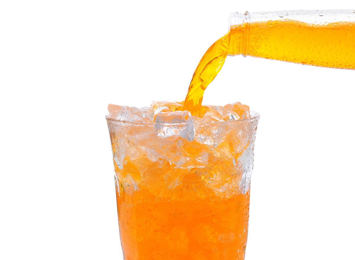 bottle of orange soda poured into glass