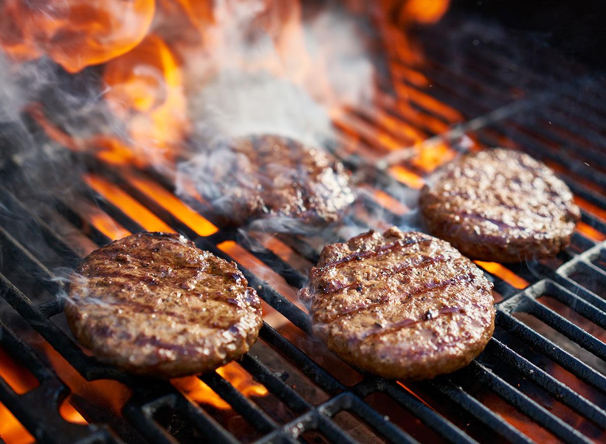 flames behind cooking burger patties