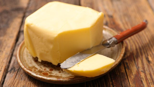 block of butter with slice out of it from knife on platter