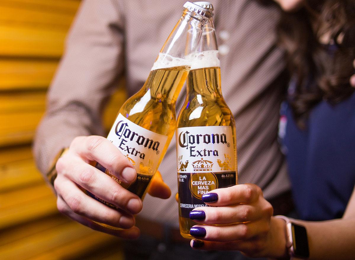 couple holding corona extra bottles most popular beer new york