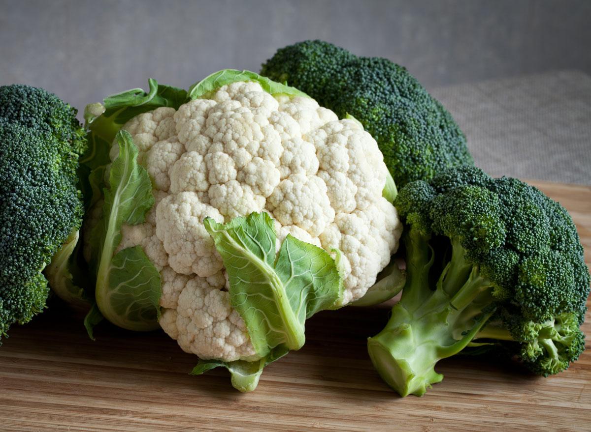 Cruciferous vegetables broccoli cauliflower on wooden cutting board