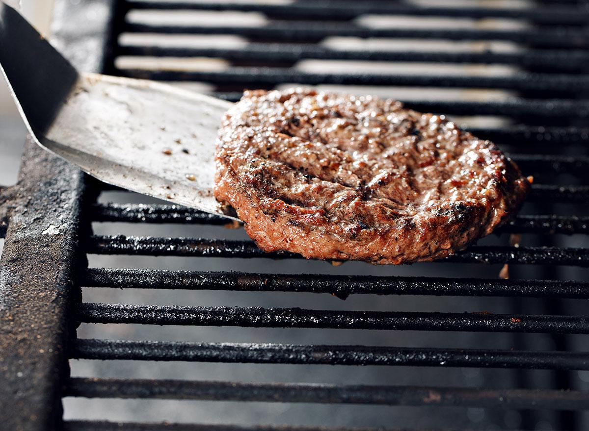 spatula flipping burger patty on grill