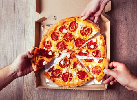 3 hands pulling slices of pepperoni pizza
