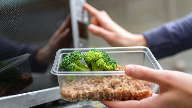 person putting container of broccoli and grains into the microwave