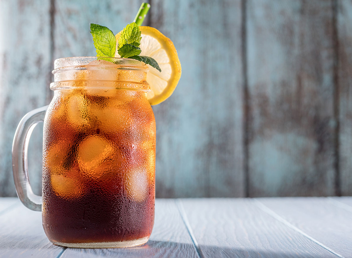 iced tea in a mason jar with a green straw, lemon wheel, and a sprig of mint
