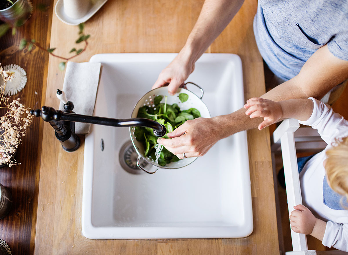 woman pouring water in kitchen sink over lettuce