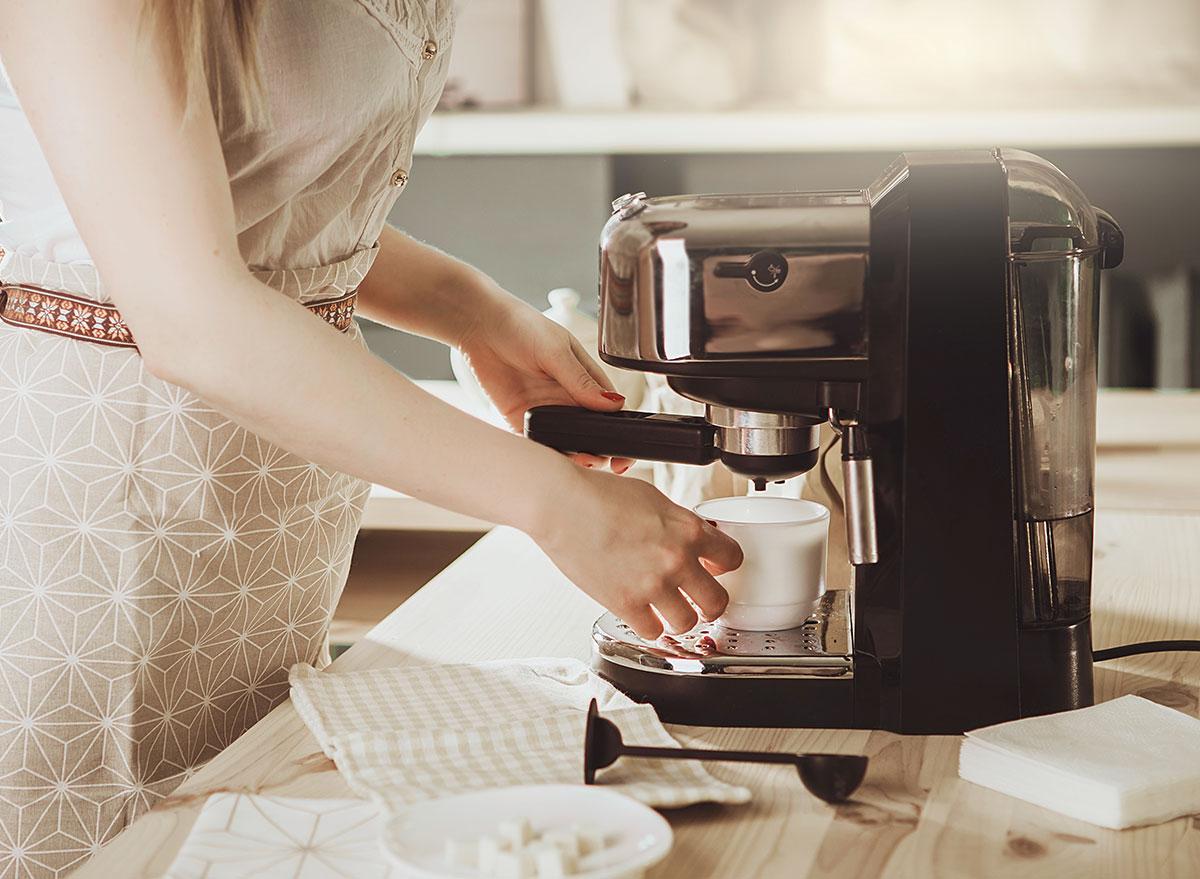 nice dressed woman using coffee machine