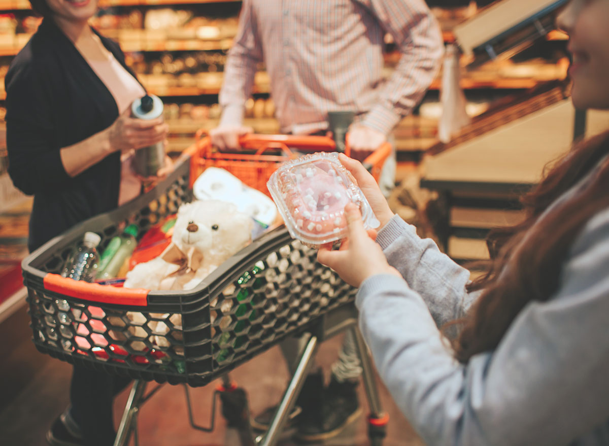 Parents grocery shopping with kid who holds doughnut