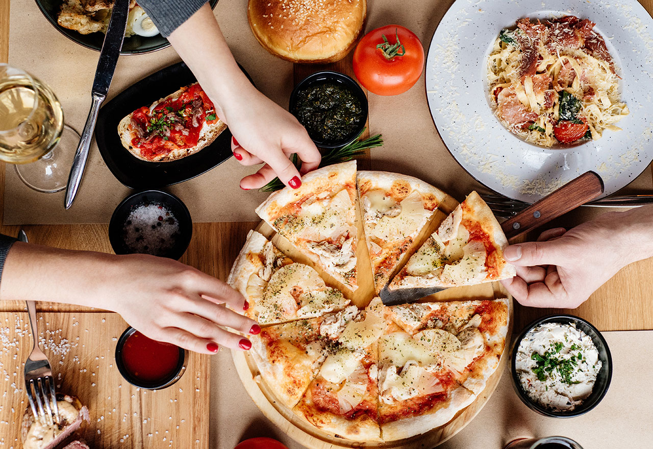 two people sharing pizza, pasta, and bruschetta