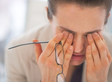 Tired stressed woman rubbing eyes