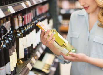 Woman looking at wine bottle label to buy