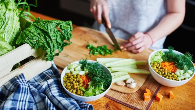 Woman chopping up vegetables to make plant based vegetarian bowl