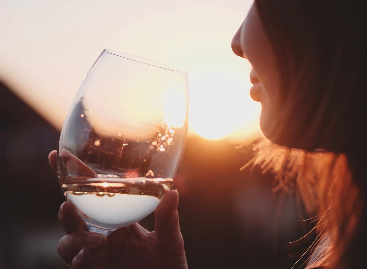 Woman drinking white wine at sunset