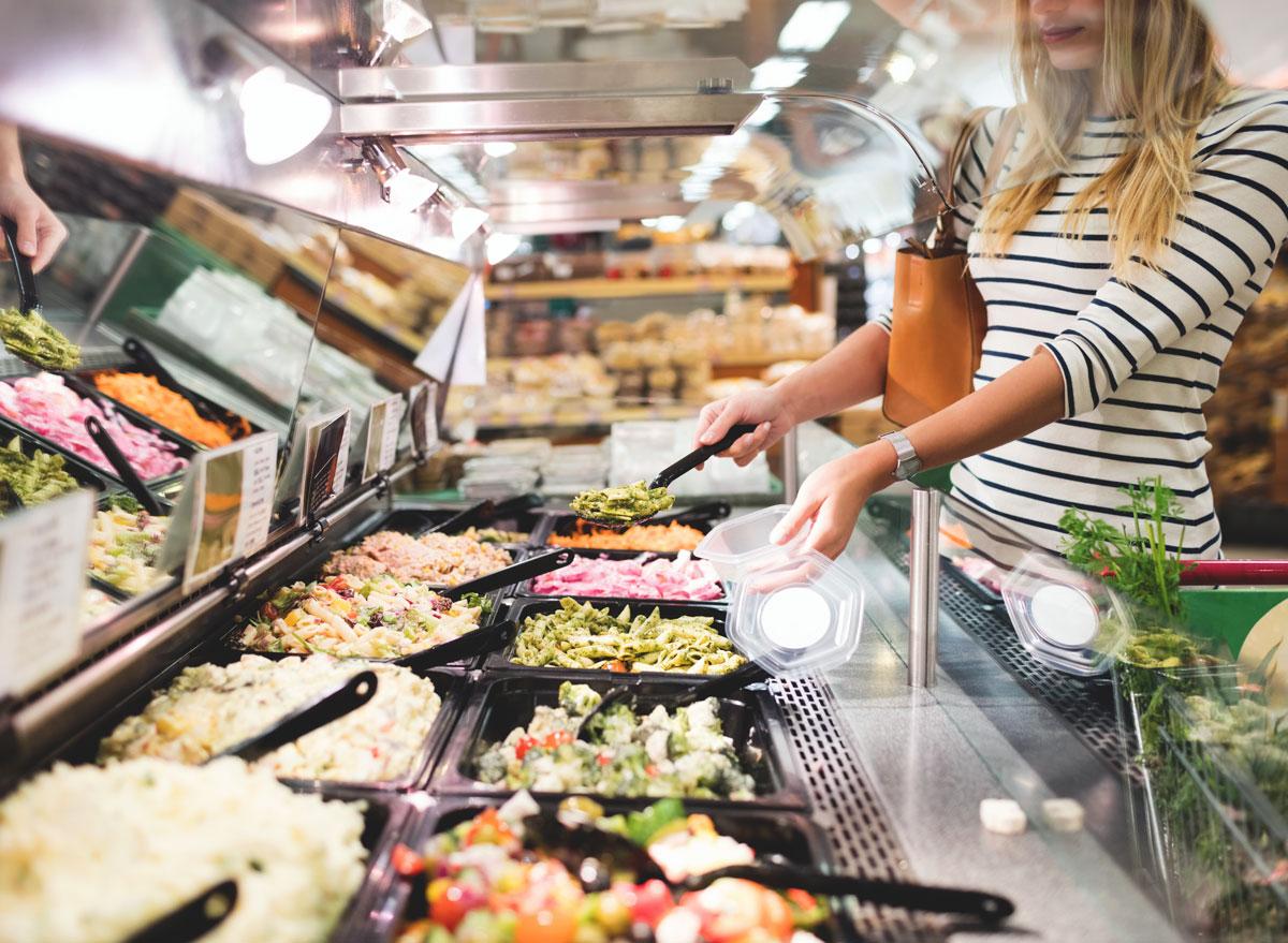 Woman at grocery store serving prepared food at salad bar
