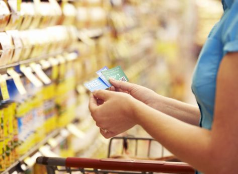 Woman holding coupons at supermarket