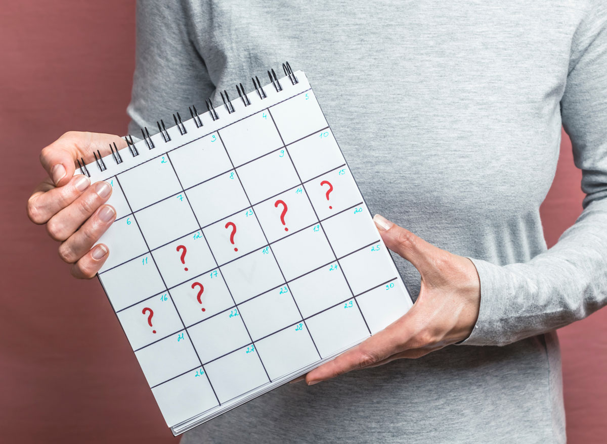 Woman holding up calendar showing late period