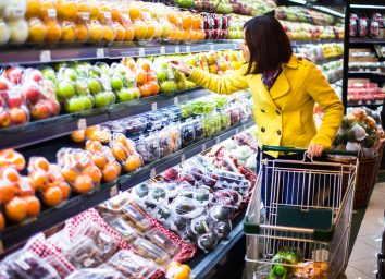 woman wearing a yellow coat scans the produce section of a grocery store