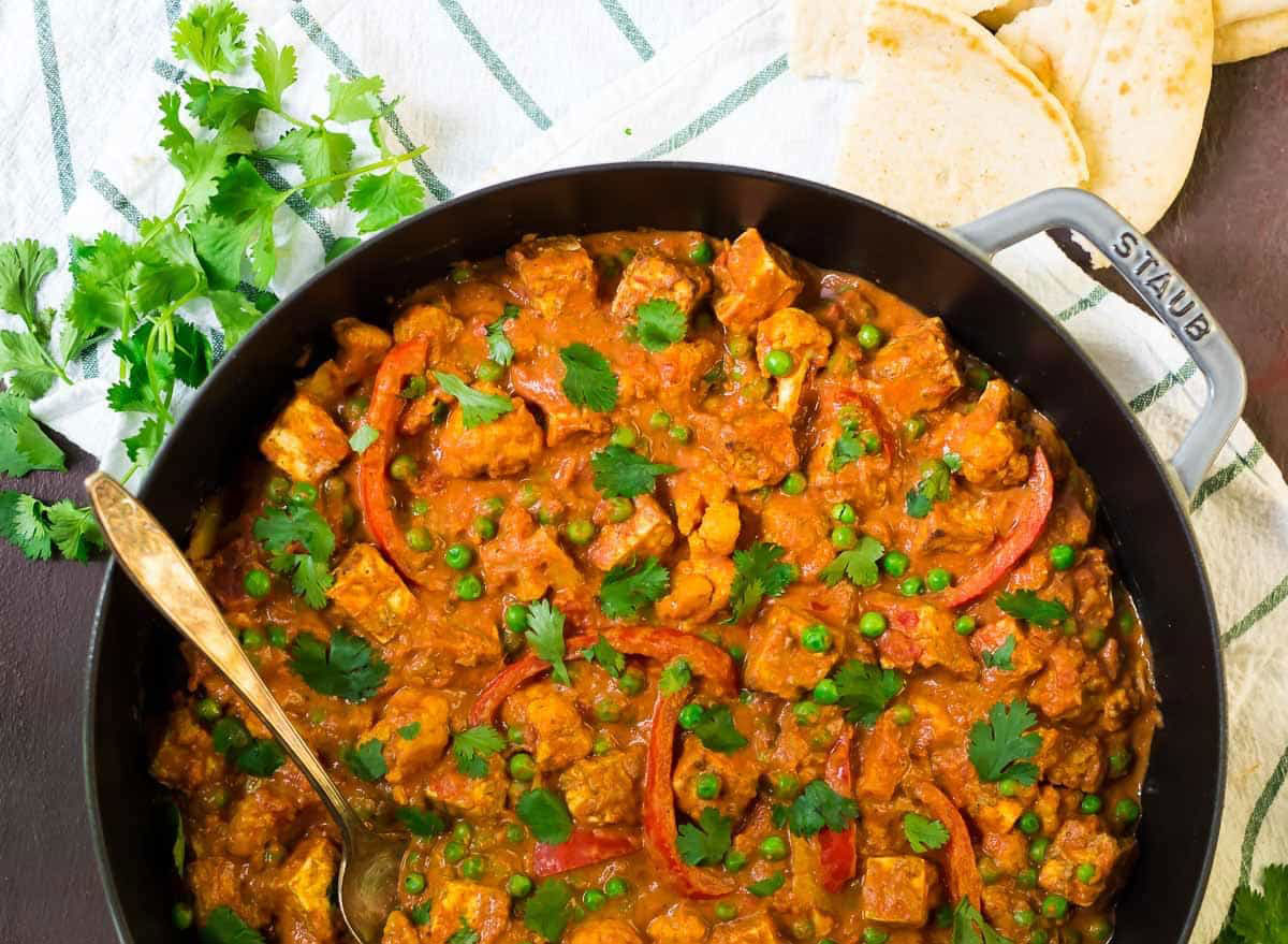 paneer tikka masala recipe with tofu on a skillet with bread and herbs