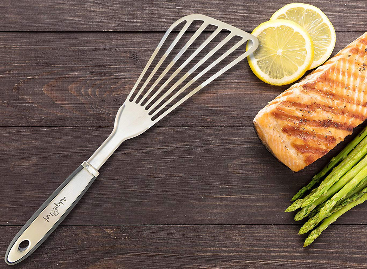 adept chef fish spatula with salmon and asparagus on a wooden board