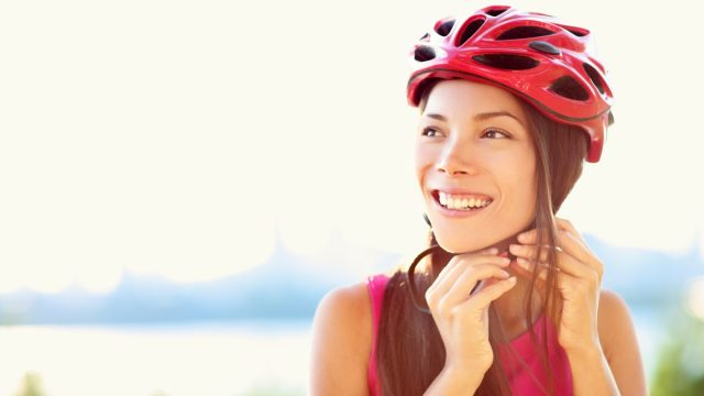 woman putting biking helmet on outside during bicycle ride