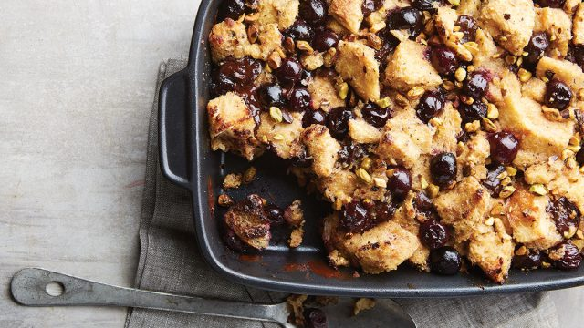chocolate cherry bread pudding with pistachios in baking tray with spoon