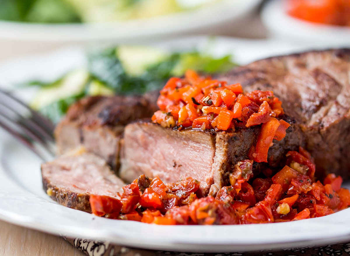 sliced medium well cooked steak dish on white plate with tomato topping