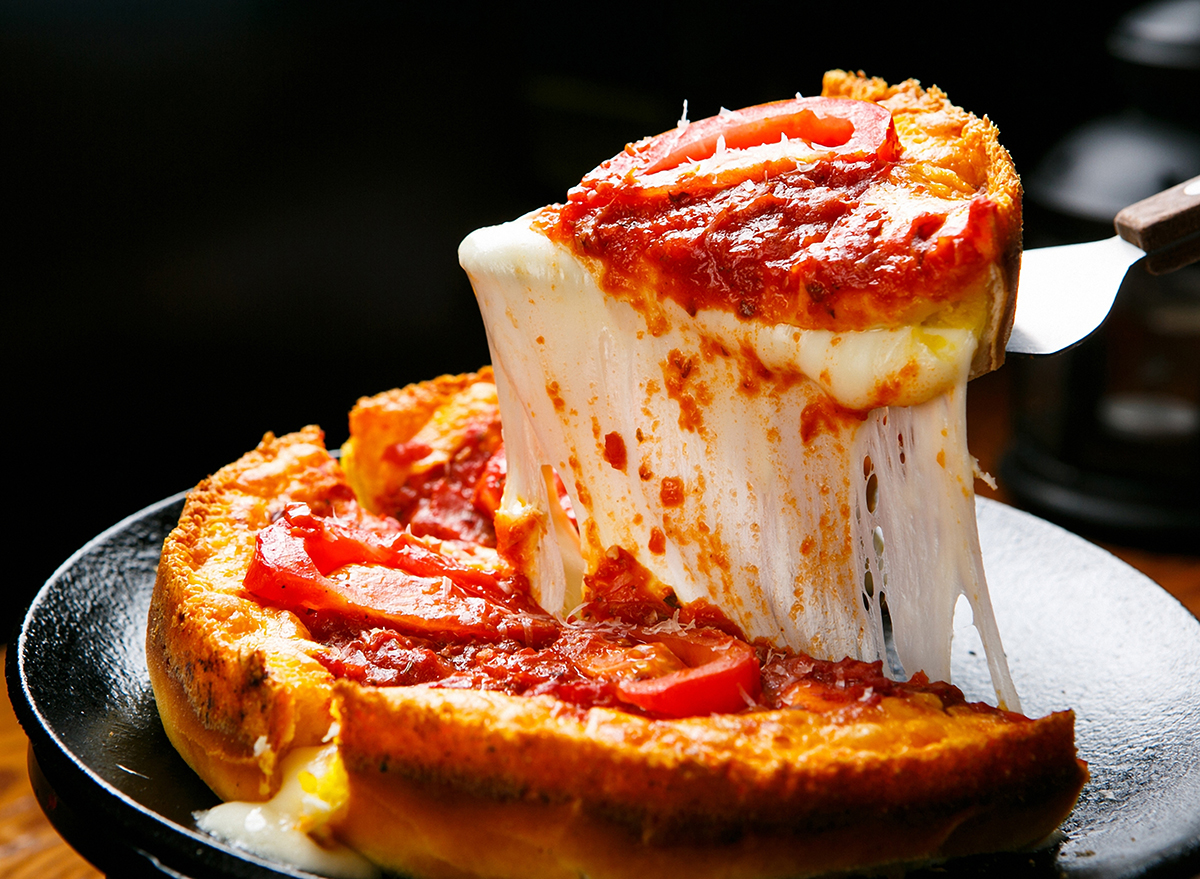 slice of deep dish pizza lifted out of pizza pan in chicago