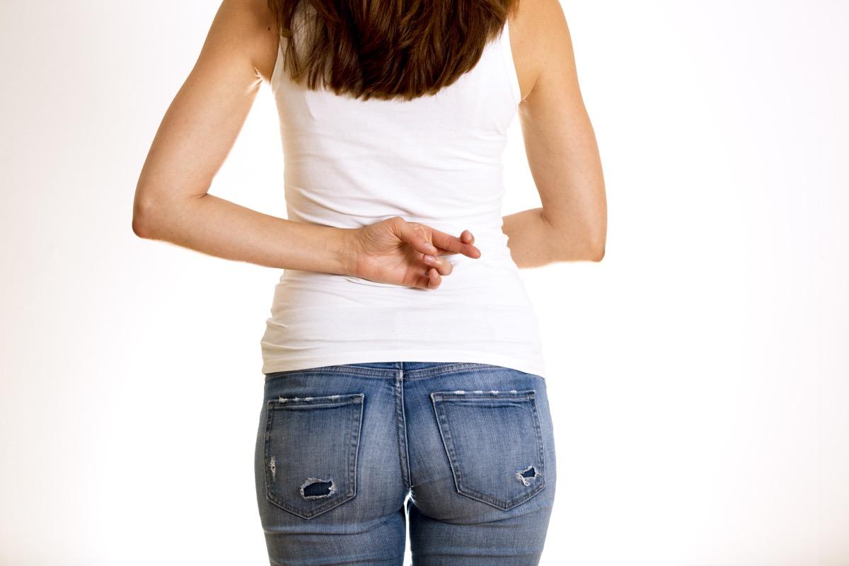 female holding fingers crossed behind her back