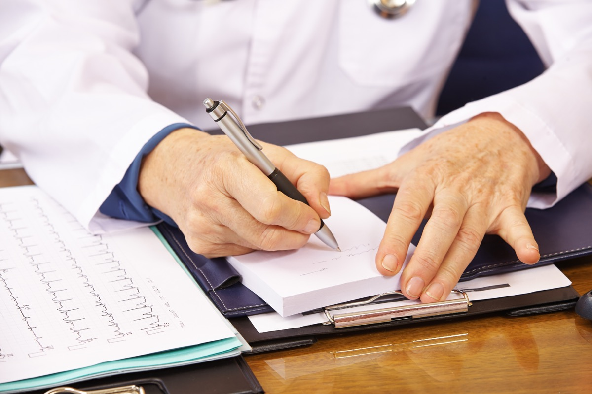 Hand of senior doctor taking notes in office