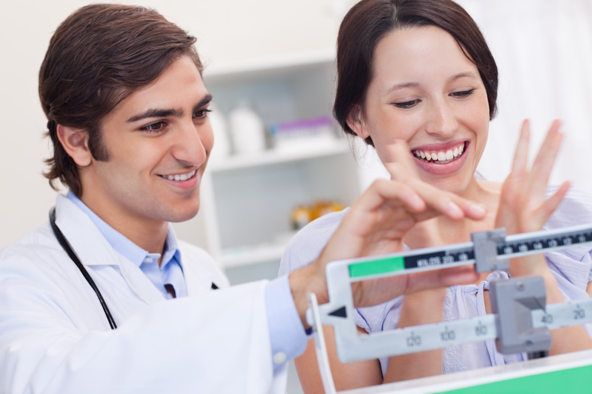 Young male doctor adjusting scale for excited patient