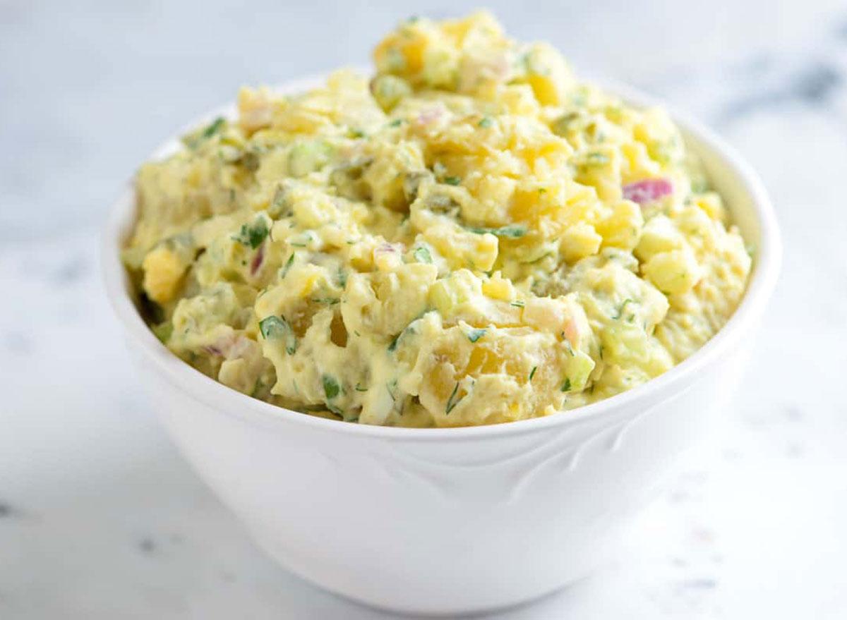 potato salad in white bowl on marble background