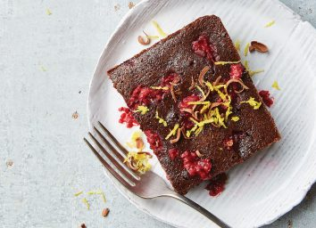 fudgy raspberry brownie on white plate with fork
